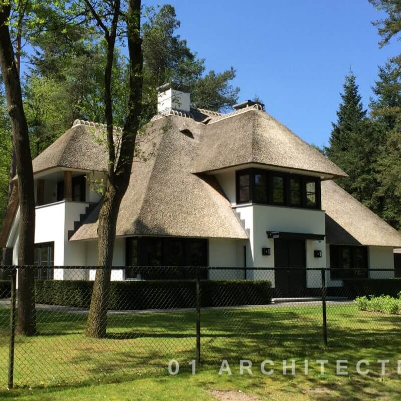 Moderne villa met donkere kozijnen, witte gevels en rietgedekt te Beekbergen
