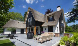 Villa met veranda zwarte eiken houten planken, houten palen en wit stucwerk en rieten kap te Blaricum