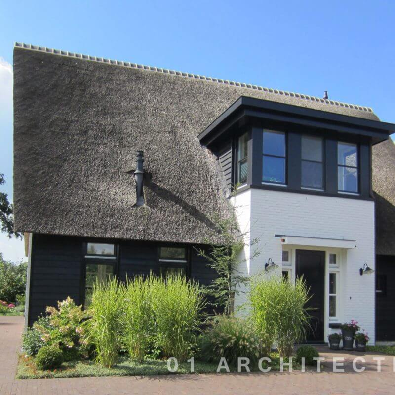 Rietgedekte nieuwbouw woning, accent door de kap met zwart houten gevel en wit geschilderde gevel