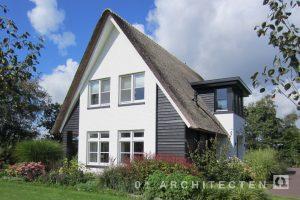 Rietgedekte woning met veranda, zwarte houten gevels en wit geschilderde gevels te Barneveld
