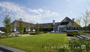 Eigentijds landhuis met witte gevel, zwarte kozijnen en riet te Emst, Gelderland