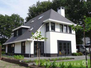 Voorgevel eigentijdse jaren 30 woning met vlakke dakpan en klassieke roedes te Veenendaal
