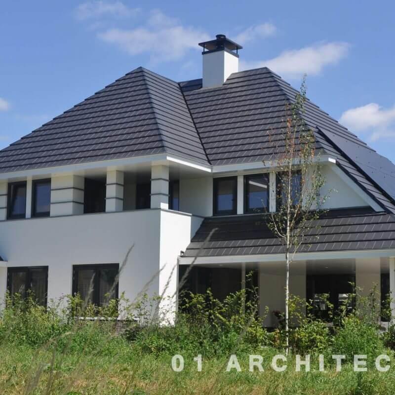 Witte villa met vlakke pannen, accentbanden in natuursteen en veranda te Ommen