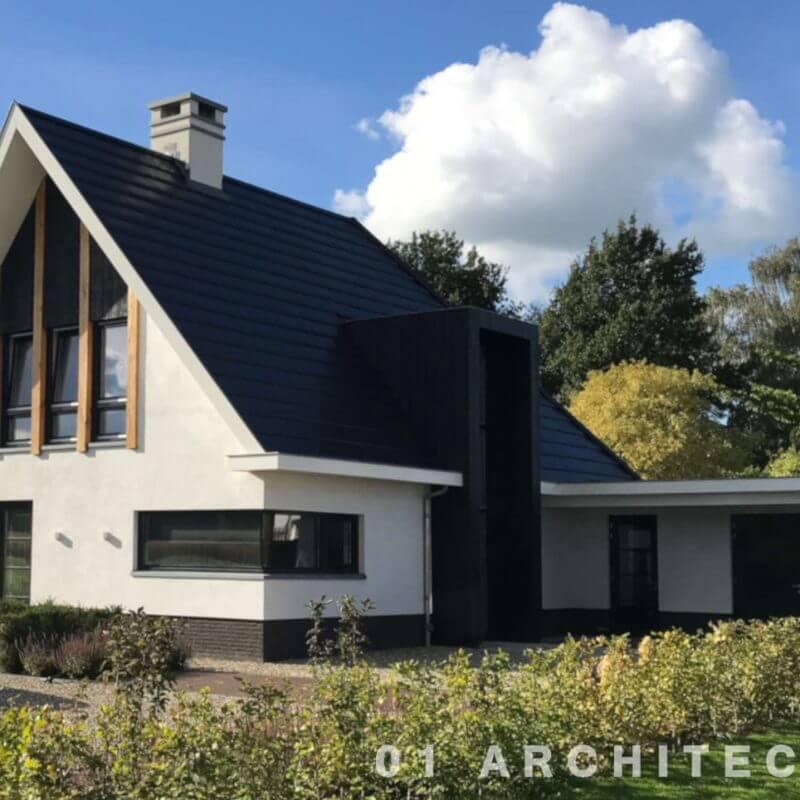 Moderne villa voorzien van een vooruitstekende kap. De entree heeft een kader, uitgevoerd in zwart hout. Het hoekkozijn is zonder kozijn uitgevoerd.