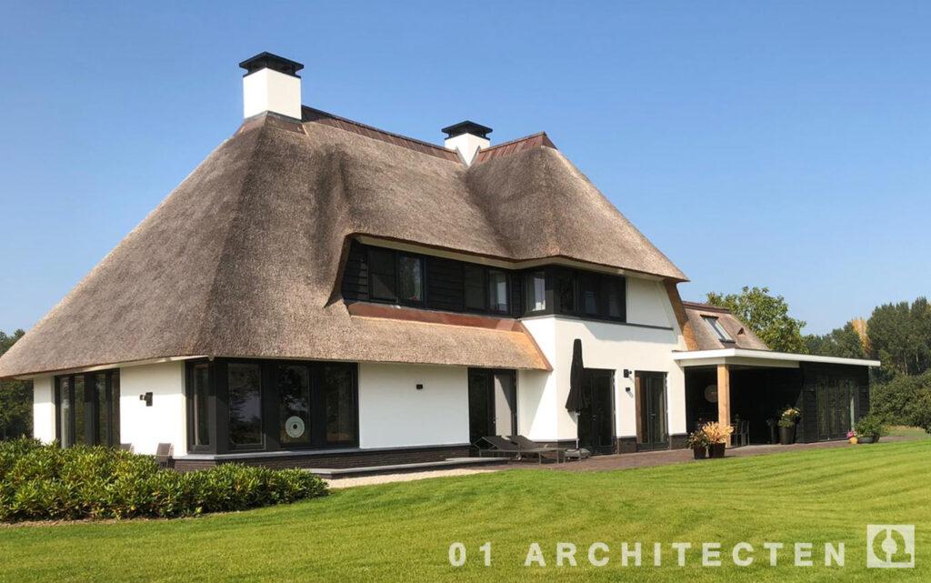 stoer breed landhuis met rieten dak en koperen noklijn met hoog en laag deel